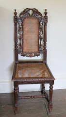A Vintage Wooden Chair with a Mesh Seat and Back.
