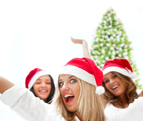 Group of three happy pretty girls are celebrating christmas and