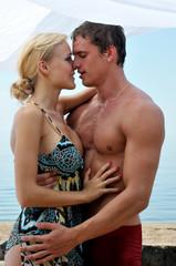 Beautiful woman and man kissing at the beach.