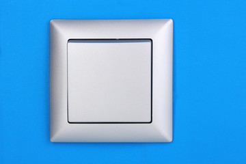 Modern light switch on blue background