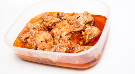 Chicken curry in a lunch box on a white background