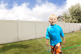 Little Boy Playing in the sprinklers. Summertime fun