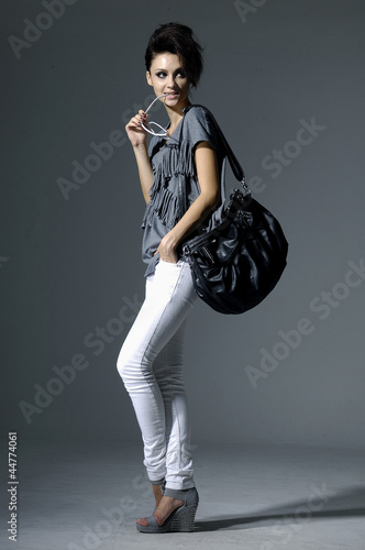 Full length Portrait of stylish professional model with handbag