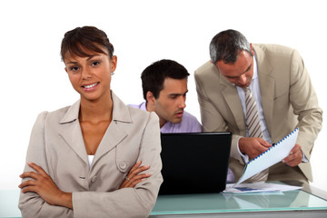 Smiling businesswoman standing in front of male colleagues