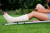 Girl with leg in plaster chatting with her smartphone