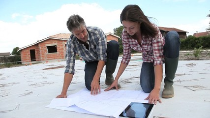 Couple checking construction plan on site