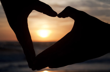 Hands forming a heart at the sunset