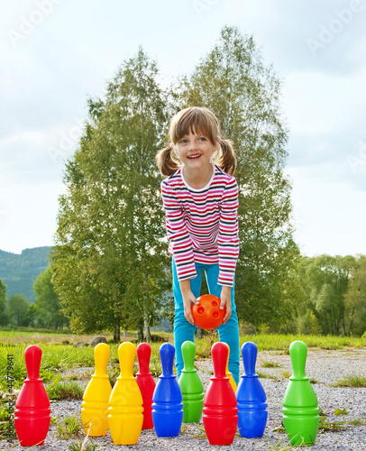 little girl playing bowling outdoor