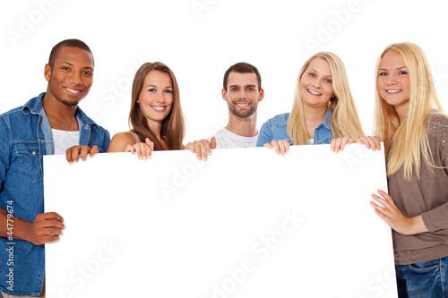 canvas print picture Gruppe junger Personen hält weißes Schild