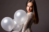Beautiful fashion woman in studio with white balloons