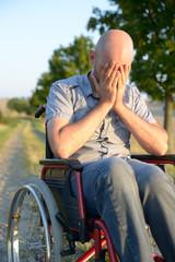 Verzweifelter Mann im Rollstuhl