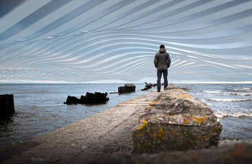 A man on the old broken pier under surreal sky