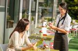 Waitress taking woman's order at cafe bar