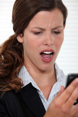 Woman staring in disbelief at her mobile phone
