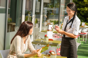 Waitress taking woman's order at cafe bar