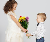 Smiling boy presenting bunch of colored flowers to charming girl
