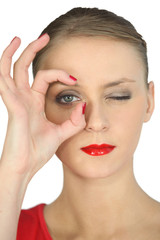 Woman making a circle with her fingers around her eye
