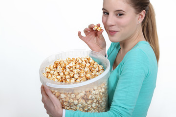 Woman eating popcorn from large bucket