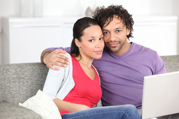 young metis couple doing computer on the couch