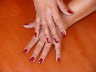 Zwei Hände mit rot lackierten Fingernägeln