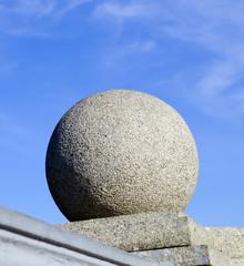 Каменный шар на фоне синего неба