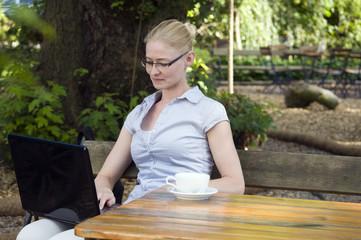 Geschäftsfrau mit Notebook im Biergarten