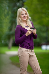 Woman Holding Smart Phone In Park