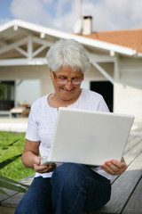 Elderly woman looking at her laptop outdoors