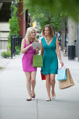 Female Friends With Shopping Bags Using Digital Tablet