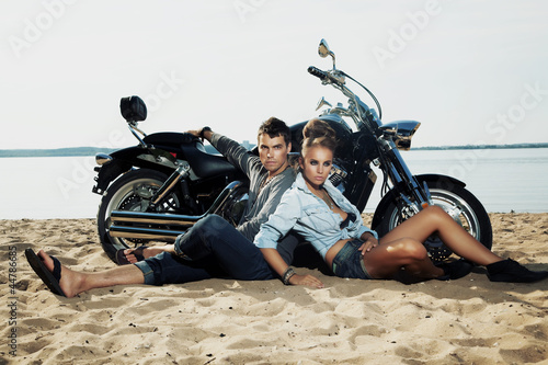 Boyfriend and girlfriend rider sitting on sand beach by bike