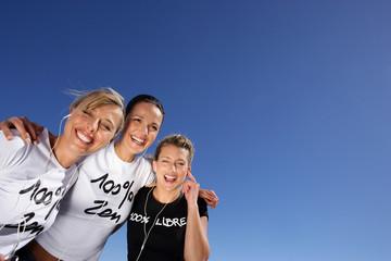 Three women stood outdoors with headphones