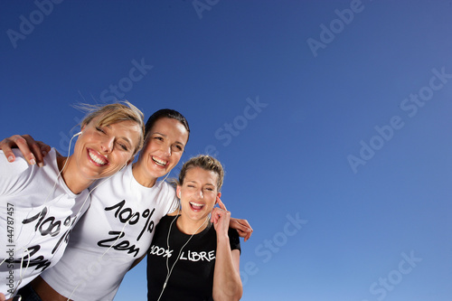 Three women stood outdoors with headphones