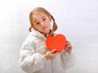 Girl in white coat showing red heart shape, isolated on white