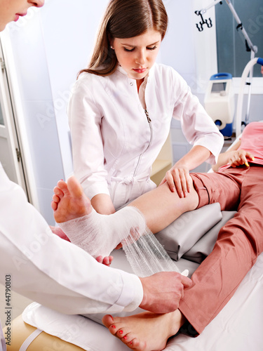 Doctor bandaging patient in hospital.