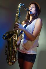 joven y atractiva mujer con gorro tocando el saxofon