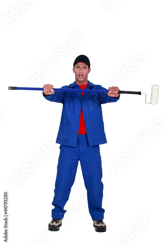 painter holding a roller on a long handle