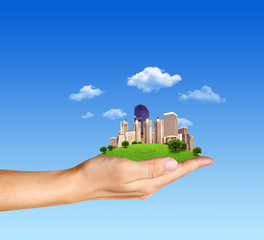 Concept human hand holding a city on green grass