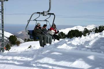 Three people sitting in a ski lift