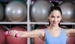 Sportive woman training with dumbbells in gym. Gymnastics