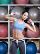 Young woman training with dumbbells in gym