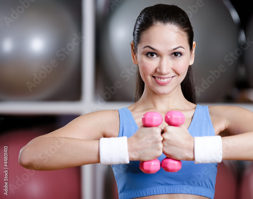Athletic woman in sportswear training with dumbbells