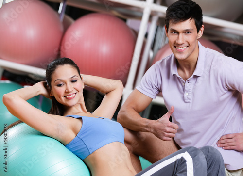 Athlete woman exercises in fitness gym with couch