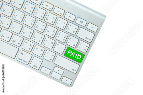 Green paid button on computer keyboard isolated on white backgro