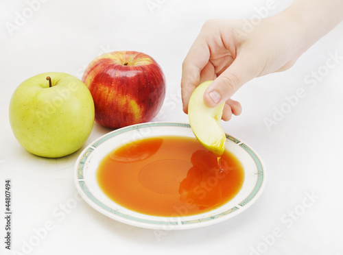hand dipping the piece of apple in honey as jewish new year sym