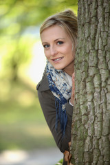 Blond stood behind tree
