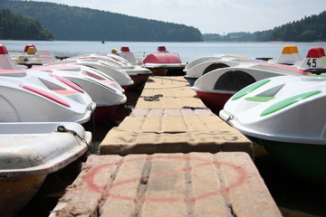 Various pedal boat docked at dam. Active recreation objects