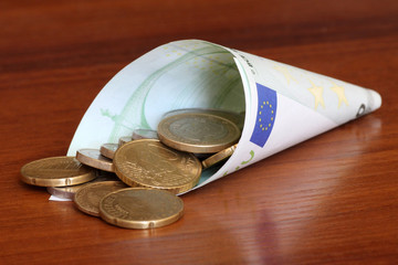 Euro coins in rolled one hundred euro banknote