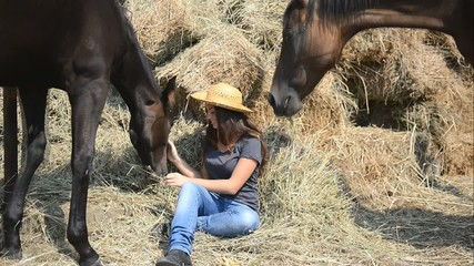 Young Beautiful Girl and her horses resting near a haystack