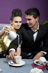 The girl pours milk in coffee of the man