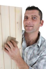 Carpenter sanding plank of wood